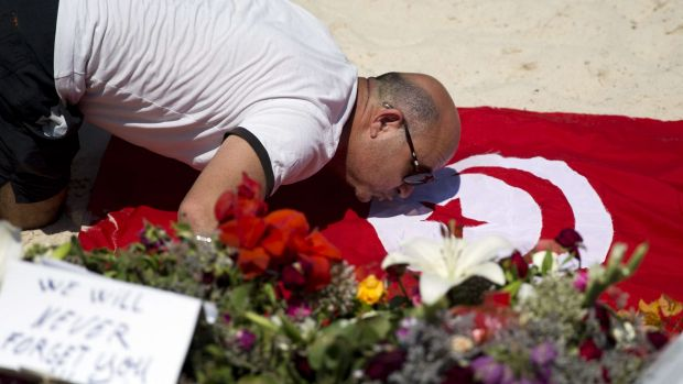 A man kisses a Tunisian flag at the site of a shooting attack on the beach in front of the Riu Imperial Marhaba Hotel in ...