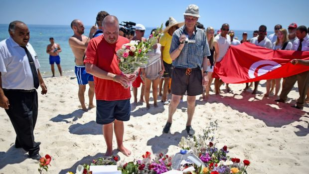 Tourists carry a Tunisian flag along Marhaba beach where 38 people were killed on Friday.
