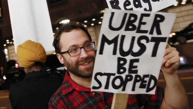 Demonstrators hold signs during a protest in San Francisco against ridesharing services Uber and Lyft.