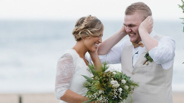 We can't hear you: Abbey and Mitchell Johnston block their ears as the Marriage Act is read out during their wedding ...