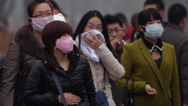 Chinese commuters wear face masks as heavy air pollution shrouds Beijing in February 2014. China's cities are often hit ...