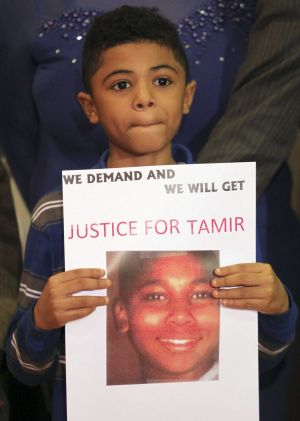 A boy holds a sign demanding action after 12-year-old Tamir Rice was fatally shot by police in Cleveland, Ohio, in ...