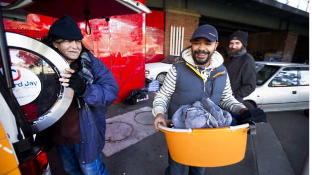 Tony Bautista (left) and Michael Jager (middle) make use of mobile van Orange Sky Laundry as Steve Cook (right) looks ...