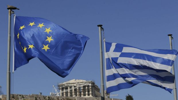 The EU and Greek flags wave under the ancient Acropolis hill in Athens.
