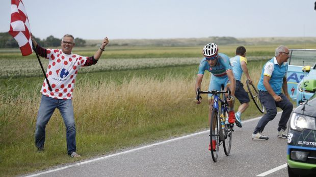 Defending champion Vincenzo Nibali gets back on his bike after puncturing in the closing kilometres of stage two after ...