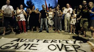 "Supporters of the ""OXI"" or ""No"" vote stand by an anti-austerity banner as they celebrate results in Thessaloniki."