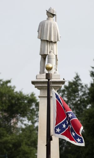 The Confederate battle flag flies next to a Civil War memorial outside the South Carolina state house.