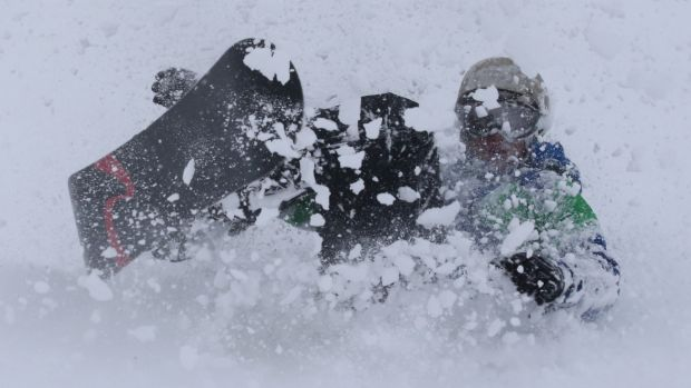 Can you tell the difference? A snowboarder enjoys a flurry on Friday.