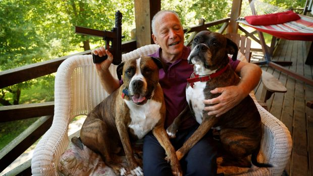 Richard Feldman at his home in Rindge, New Hampshire with his dogs Stanley and Stella and a version of the TEC-9.