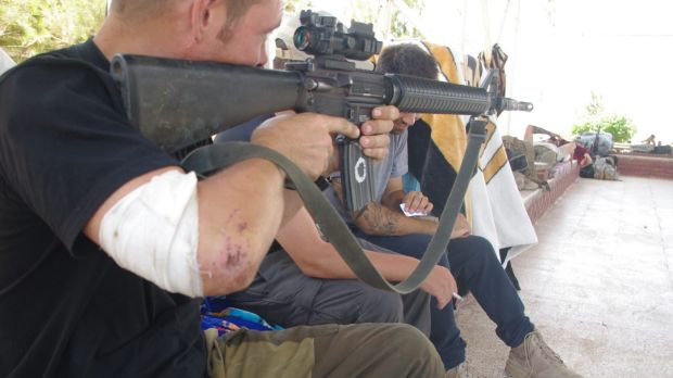 Siyar points an M-16 as another western volunteer sits between him and Rob, whose face is obscured by the barrel.