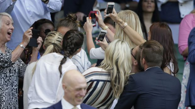 People pose for a selfie with British former soccer player David Beckham at Wimbledon.