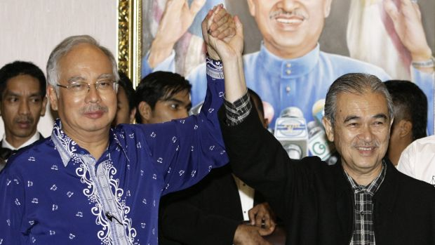 Former Malaysian Prime Minister Abdullah Ahmad Badawi holds hands with his then deputy Najib Razak (left) in 2008.