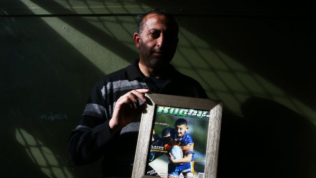 Azzam Hrouk, father of Mahmoud Hrouk, poses with a picture of his murdered son.