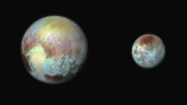 A combination image released by NASA on July 13 shows Pluto, left, and its moon, Charon, with differences in surface ...
