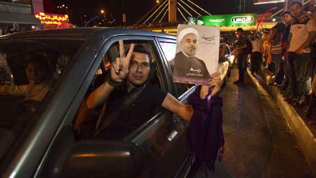 A man holds a picture of Iran's President Hassan Rouhani as he celebrates the nuclear deal with others in the streets.