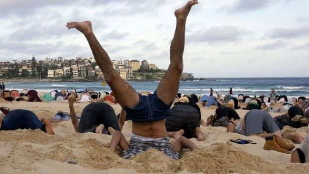 Australians bury their heads in the sands of Bondi Beach to send a message to Prime Minister Tony Abbott about the ...