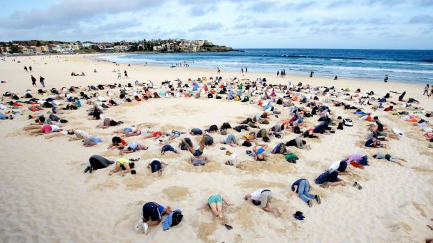 More than 400 people gather at Bondi Beach to bury their heads in the sand to send a climate change message to Prime ...