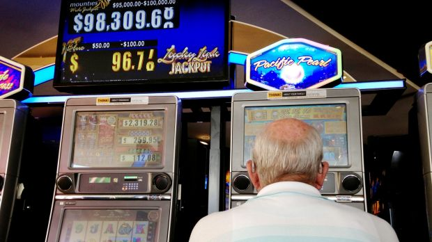 A man plays the pokies at Mounties Club in Mount Pritchard in the City of Fairfield, whose residents wagered nearly $8.5 ...