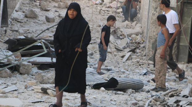 Civilians walk on rubble as they inspect a site hit by what activists said was a barrel bomb dropped by forces loyal to ...