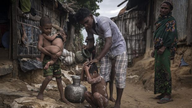 A Rohingya man bathes his child at the Kutupalong Refugee Camp in Teknaaf, Bangladesh.