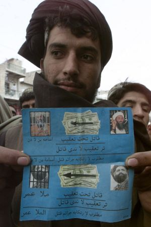 "An Afghan shows leaflets dropped by US  planes along the Afghan-Pakistan border in March 2003 reading ""Chase Murderers"" ..."