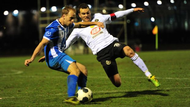 Right, Dustin Wells of Gungahlin United FC attempts to tackle Brayden Sorge of Sydney Olympic FC.