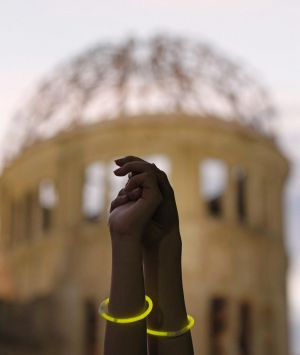 Two women hold hands after forming a human chain to surround the gutted Atomic Bomb Dome in Hiroshima during an event to ...