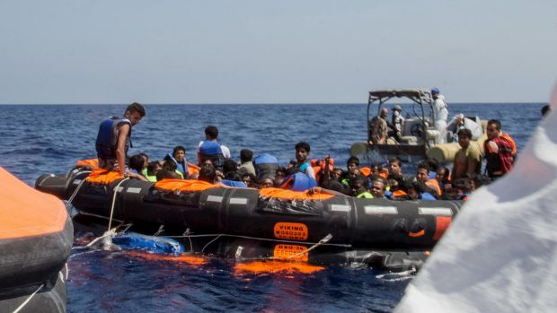 Surviving migrants are brought aboard Irish and Italian Navy life-boats in the area where their wooden boat capsized and ...