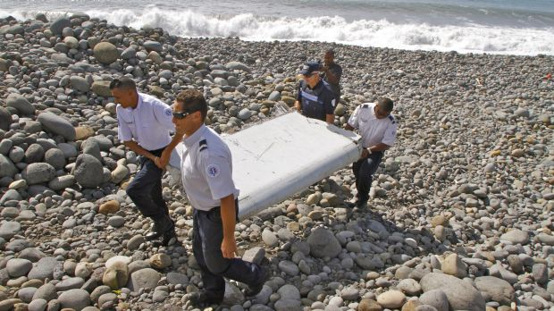 French police officers carry the piece of a wing confirmed as from MH370.
