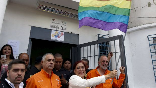 Tamara Adrian, holds a LGBT flag as she arrives to register her candidacy for the upcoming parliamentary elections.