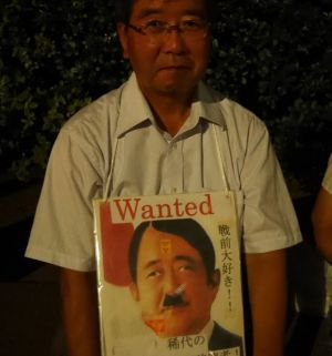 A protester with a sign showing Japanese PM Shinzo Abe as World War II Nazi dictator Adolf Hitler.