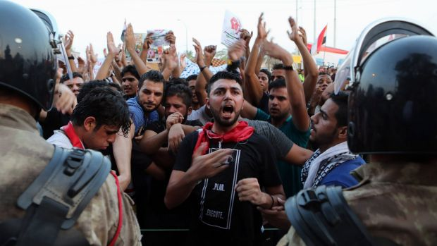 Protesters chant anti-government slogans while riot police guard the provincial council building during a protest ...