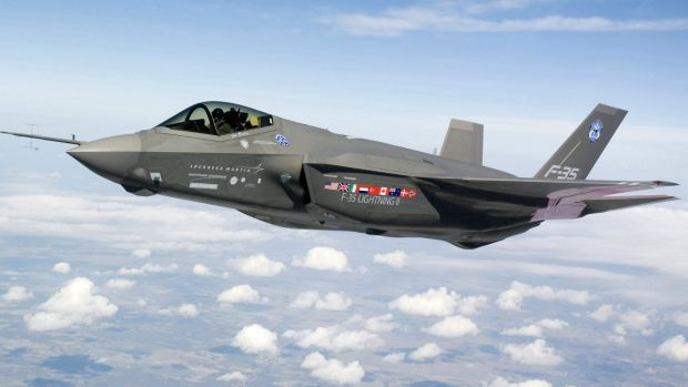 An F-35 Lightning II makes a test flight over Fort Worth, Texas, in 2008. The Canadian flag can be seen next to ...