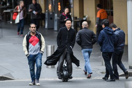 A man rides his airwheel through the streets of Sydney.