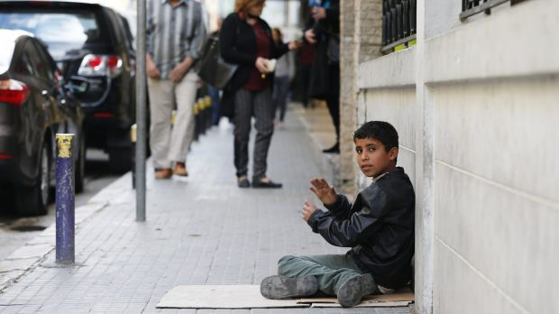 A Syrian boy sits on a footpath as he begs for money in Beirut.