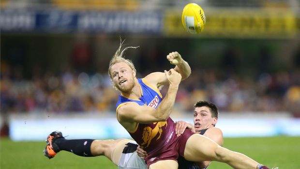 Daniel Rich of the Lions handballs as he is tackled by Matthew Kreuzer of the Blues.