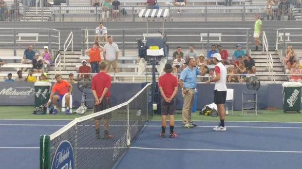 The chair umpire speaks with Thanasi Kokkinakis during his game against Ryan Harrison.