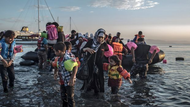 Syrian refugees wade ashore after arriving via a motorised inflatable raft on the island of Kos in Greece.
