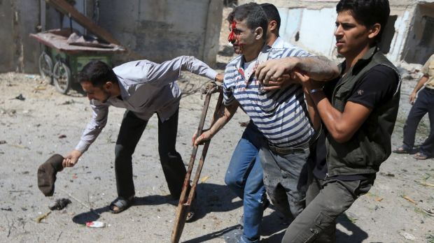 Men help an injured civilian after what activists said were air strikes by forces loyal to Syrian President Bashar ...