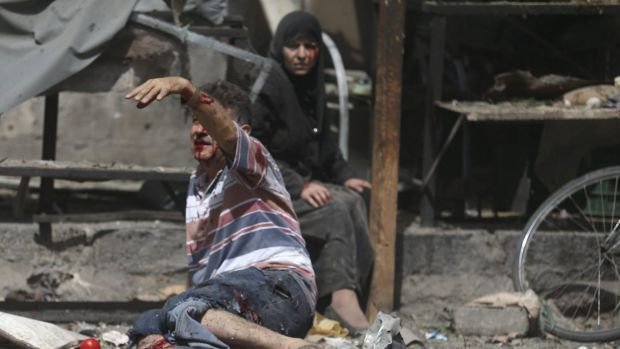 An injured man gestures as he sits near a wounded woman after air strikes on the Douma marketplace.