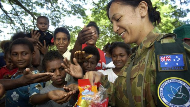 Corporal Aspen Williams hands out Christmas presents to local children presents for Christmas in a small village on the ...