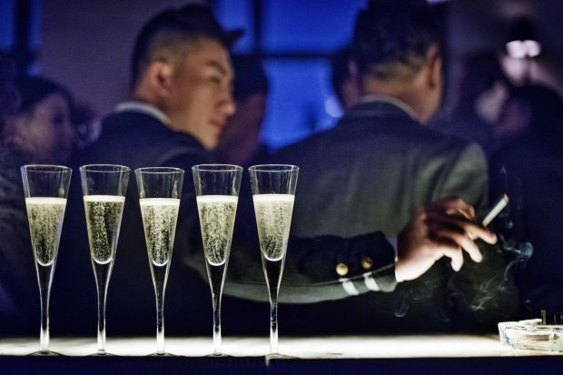 A man ashes his cigarette at the bar lined with glasses of champagne during the cocktail reception at the Black Swan ...