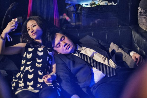 A female guest sits on a couch and takes a 'selfie' while her date snoozes on her shoulder at the Black Swan party at ...