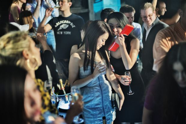 Two young women chat inside a crowded elevated section for VIP customers at Hollywood nightclub in the former French ...