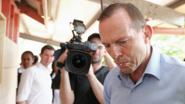 Prime Minister Tony Abbott, nail in his mouth, gets to work helping to build a cubby house during his visit to Bamaga ...