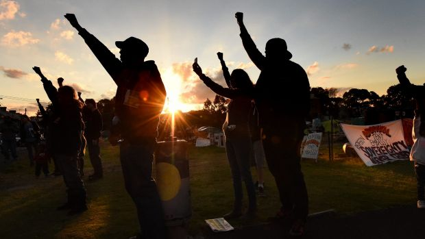 Aboriginal men and women raise their arms in support at the Block in Redfern before negotiations resolved the dispute.