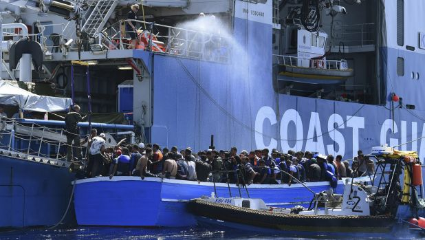 Some of the 441 refugees attempting to cross from Libya to Europe on a wooden boat are rescued by the Swedish Coast ...