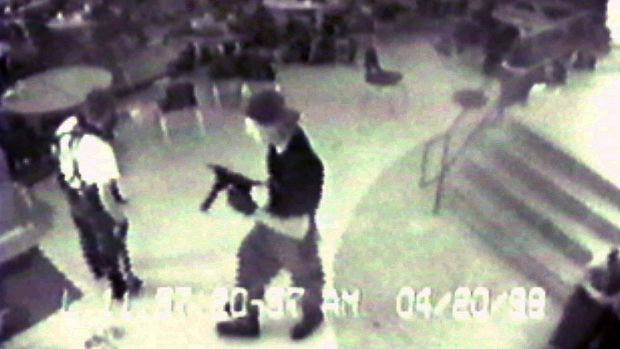 Eric Harris, left, and Dlyan Klebold, carrying a TEC-9 semi-automatic pistol, are pictured in the cafeteria at Columbine ...