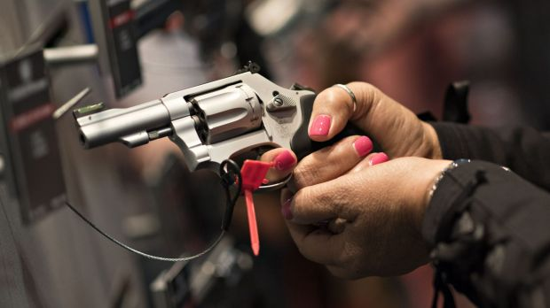 A woman handles a gun at the National Rifle Association annual show in Nashville in 2015.