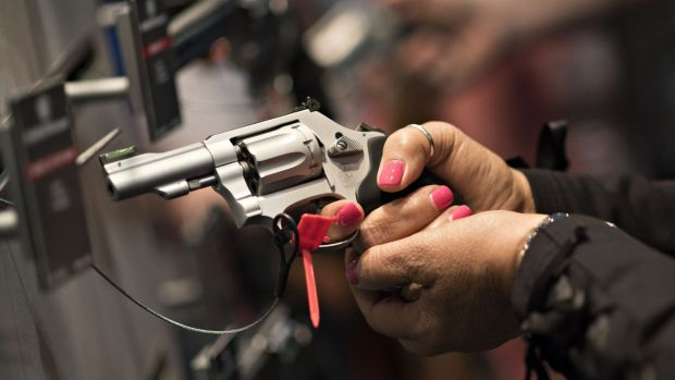 A woman handles a gun at the National Rifle Association annual show in Nashville in April.